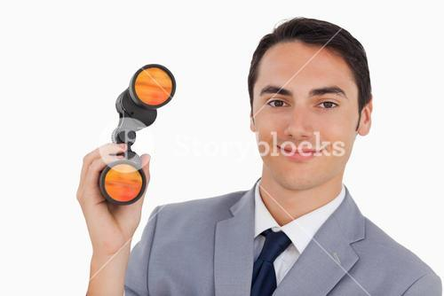 Close up of a smiling businessman with binoculars