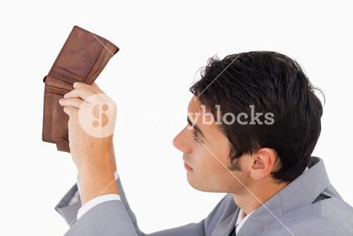 Man in a suit looking in his empty wallet