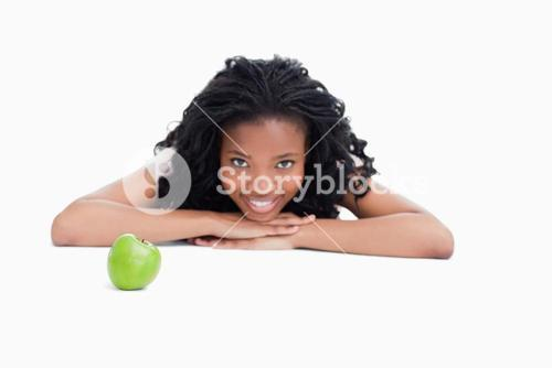A smiling girl is resting her head on her hands with an apple in front of her