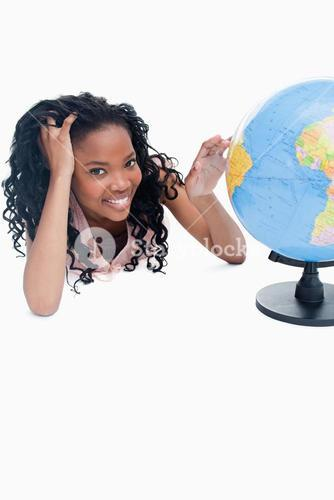 A young girl with her hand on a globe