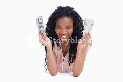 A young woman is holding American dollars and smiling at the camera