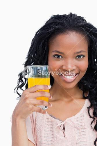 A smiling young woman holding a glass on orange juice