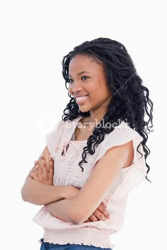 A smiling young woman with her arms folded looking away from the camera