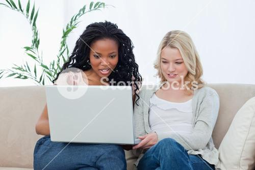 Two women sitting down looking at a laptop