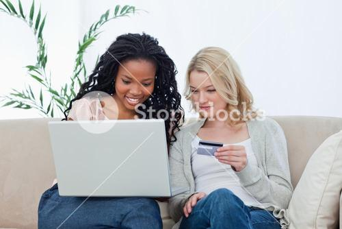 Two women are buying over the internet with a bank card