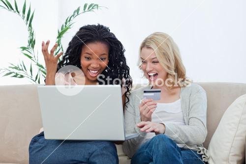 Two laughing women with a laptop and a bank card