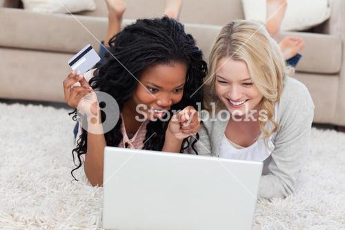 A woman holding a bank card is lying on the floor with her friend and a laptop