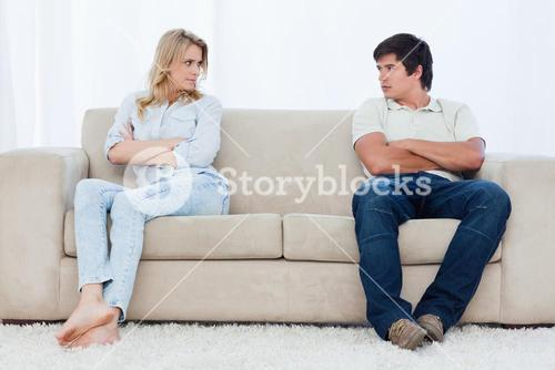 A couple sit at the two ends of the couch with their arms folded looking at each other