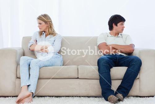 A couple sit at the two ends of the couch with their arms folded looking away