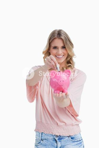 Smiling woman putting money into a piggy bank that she is holding