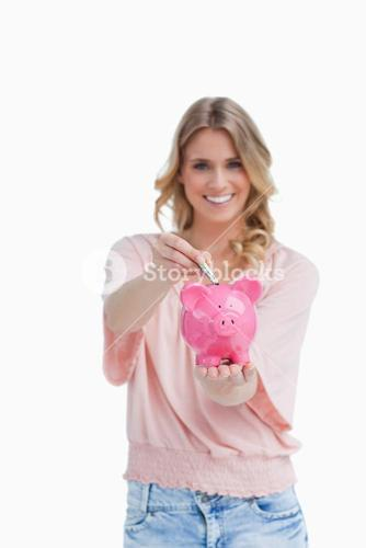 Woman holding a piggy bank is putting money into it