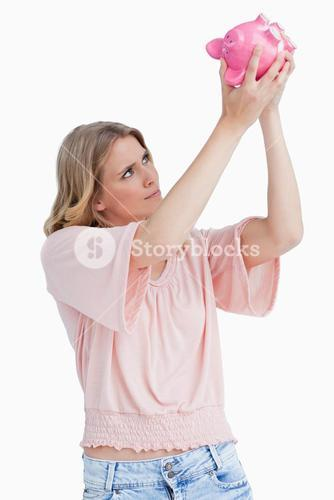 Woman looking inside of a piggy bank