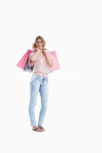 A woman is carrying shopping bags over her shoulder