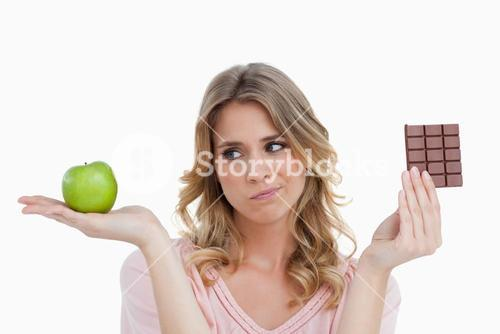 Young blonde woman hesitating between chocolate and an apple