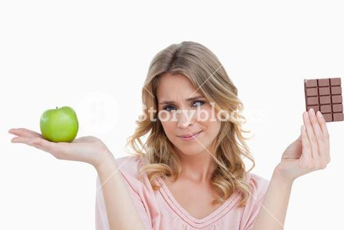 Young blonde woman holding an apple and a chocolate bar