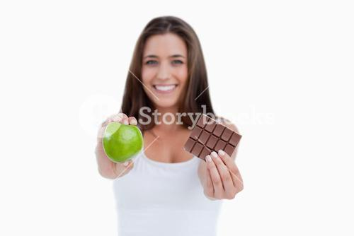 A green apple and a piece of chocolate being held by a woman