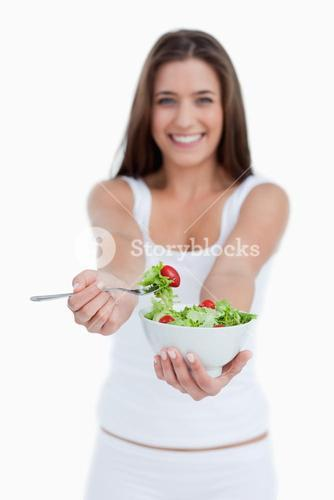 Delicious salad being eaten by a young woman