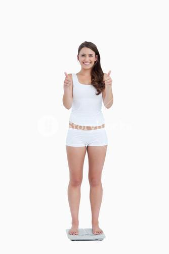 Smiling woman with her thumbs up while standing on weighing scales