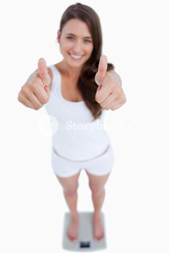Smiling woman placing her thumbs up while weighing herself