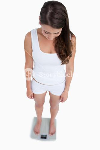 High angle view of a brunette woman weighing herself