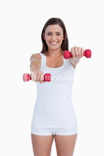 Red weights being held by a young brunette