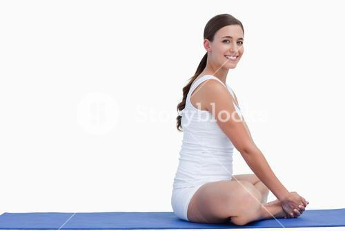 Young woman looking at the camera while sitting on a mat