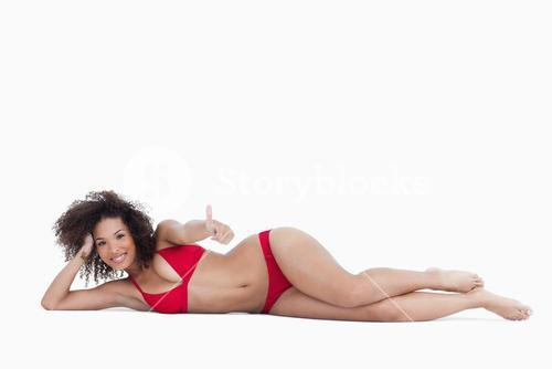 Smiling woman lying down while placing her thumbs up