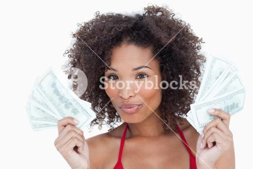 Attractive brunette puckering her lips while holding a fan of notes