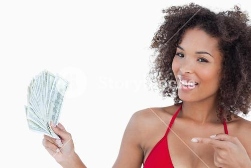 Smiling woman pointing a fan of notes
