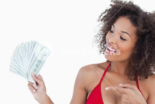 Smiling brunette woman pointing a fan of dollar notes