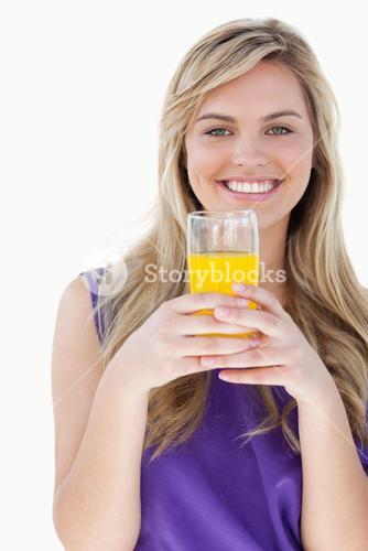 Smiling blonde woman holding a glass of orange juice