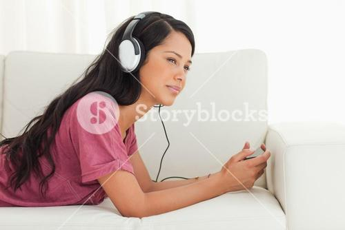 Young Latino listening music with a blank stare