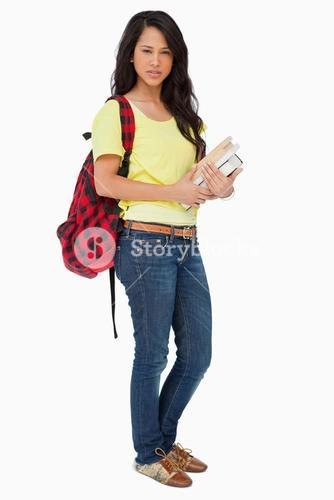 Beautiful woman student with backpack holding textbooks