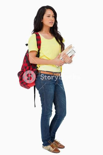 woman student with backpack holding textbooks