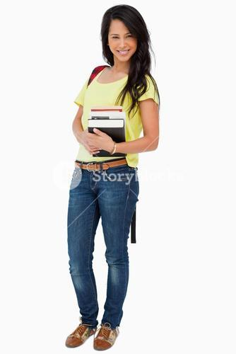 Portrait of a beautiful woman student with backpack holding textbooks