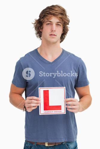 Young man holding a learner driver sign