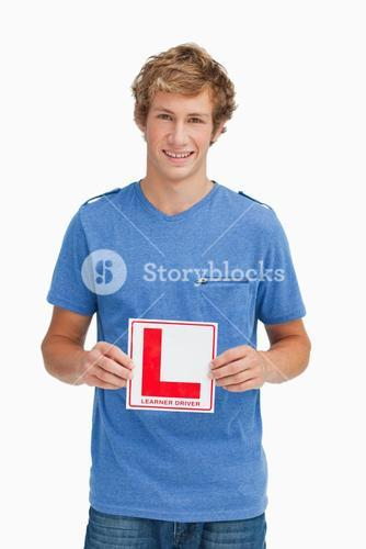 Young blond man holding a learner driver sign