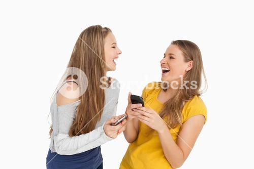Two young women laughing while holding their cellphones