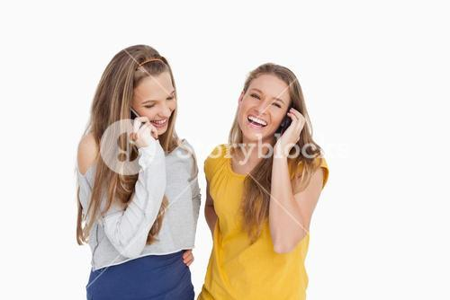 Two young women laughing on the phone