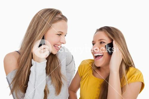 Close up of two young women laughing on the phone