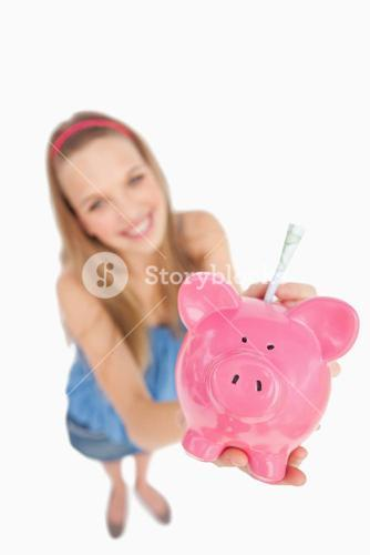 Fisheye view of a young woman putting money in a piggybank