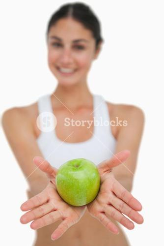 Close up a green apple holding by a brunette