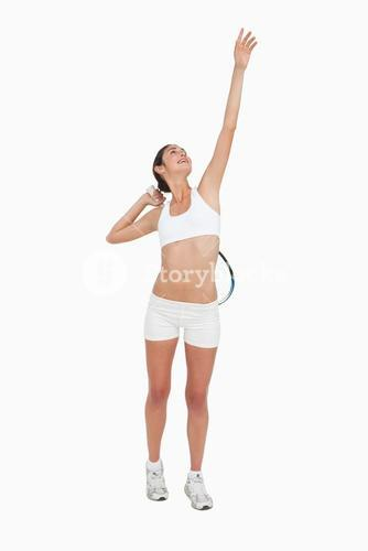 Slim woman playing tennis in white clothes