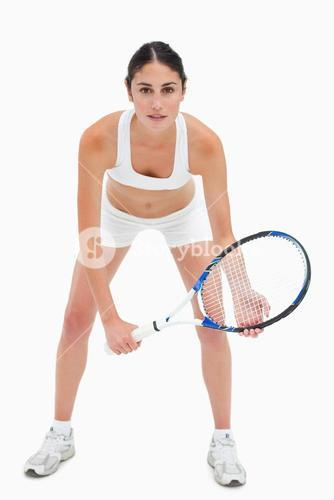 Slim young woman playing tennis in white clothes