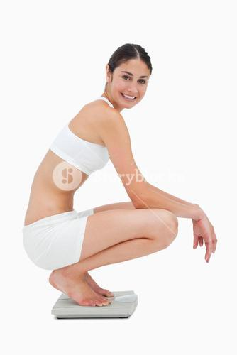 Slim young woman smiling while sitting on a scales