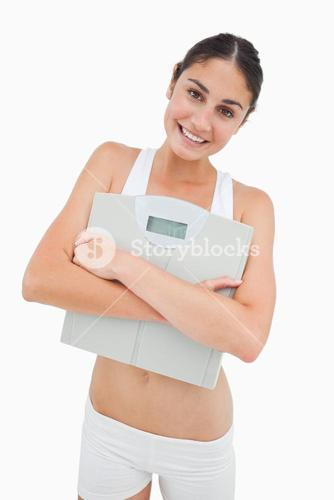 Smiling young woman hugging a scales
