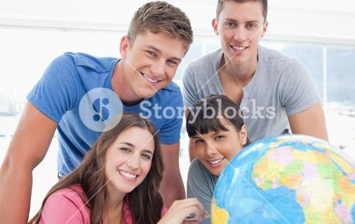 A smiling group of people looking into the camera with a globe beside them