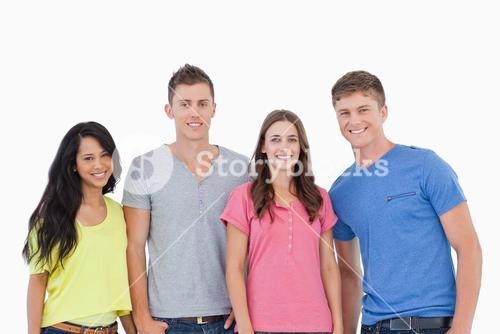 Four people standing beside one another and smiling