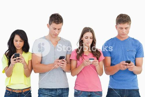 Four people standing beside each other and texting on their phones