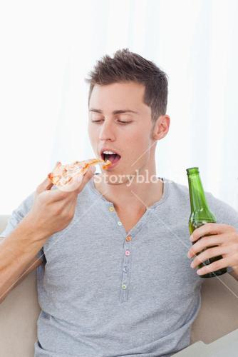 A man with a piece of pizza and some beer in his hands